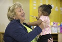 A volunteer plays with a young girl at the St. Benedict Center for Early Childhood Education in Louisville, Ky.