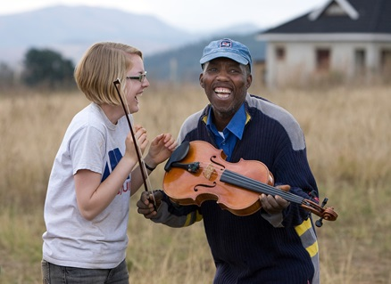 After a week spent teaching volunteers how to lay a concrete foundation in Lomngeletjane, Swaziland, builder John Dlamini receives an impromptu viola lesson from Hannah Plummer of Belmont United Methodist Church in Nashville, Tenn. Photo by Mike DuBose, UM News.