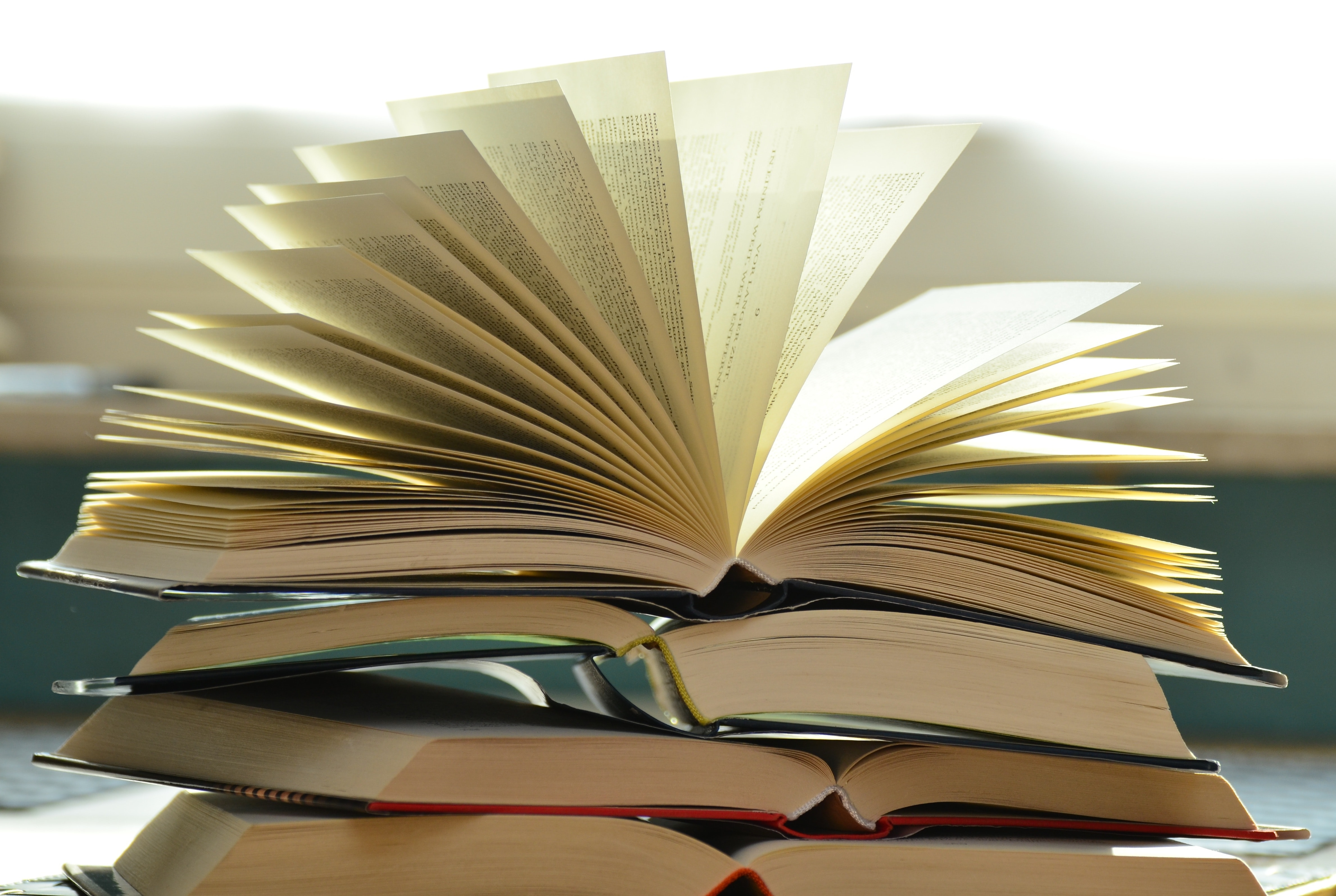 A stack of open books with a blurred background. Photo from Pixabay via Pexels.com.