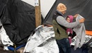 "Jesús, a migrant from Michoacán state in Western Mexico, tries to shield his 1-year-old daughter, Kataleya, from a cold drizzle falling at the tent encampment where they are living at the foot of the Paso del Norte Bridge in Juárez, Mexico. Michoacán is among five states in Mexico given the highest-risk ""do not travel"" warning by the U.S. State Department."