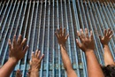Parishioners of the Border Church in Tijuana, Mexico, lift their arms skyward beneath the  fence that marks the border with the U.S. The Methodist Church of Mexico and The United Methodist Church in the U.S. share communion each Sunday across the fence.