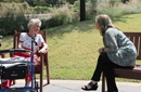 The Rev. Kellie Sanford (right) practices social distancing while visiting with a resident of the CC Young Senior Living community in Dallas. Sanford, a licensed local pastor in The United Methodist Church, serves as chaplain for the facility. Photo by Jennifer Griffin.